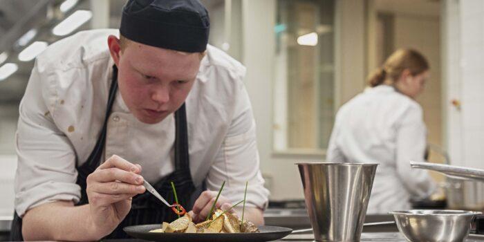 Een Student Van ROC Mondriaan Bereidt Een Gerecht Met Scheveningse Noordzeevis Voor.